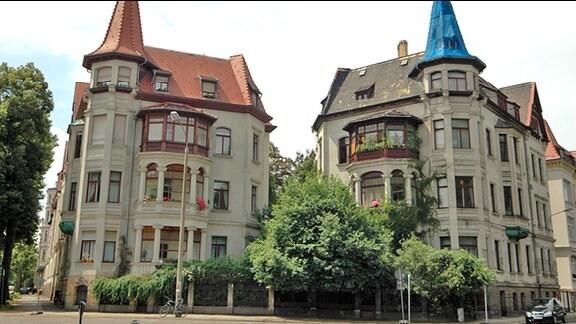 Dreistöckige Zwillingshäuser mit Türmchen, Balkons und Veranda aus der Gründerzeit an der Kreuzung Liviastraße/Feuerbachstraße/Tschaikowskistraße im Waldstraßenviertel in Leipzig, Aufnahme vom Juli 2014. Das linke Haus ist saniert, das Türmchen des rechten Hauses ist mit blauer Folie überspannt.