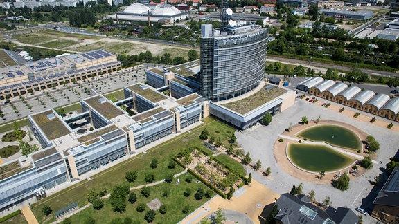 Luftaufnahme von 2013 vom größten Teil des Geländes der MDR-Zentrale in Leipzig unter anderem mit Hochhaus und Feuerlöschteich. Nebenan ist die Mediacity zu sehen. Im Hintergrund Hallen der Alten Messe.
