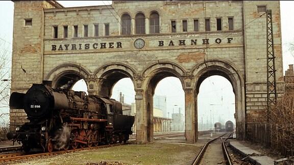 Portikus des Bayerischen Bahnhofs in Leipzig im März 1980, durch den eine Dampflok fährt