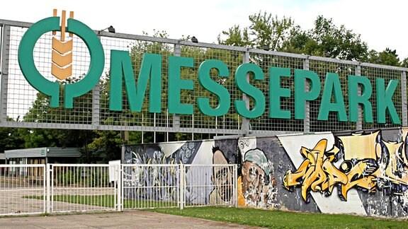 """Eingang zum Agra Messepark in Markkleeberg bei Leipzig. Die weißen Zauntore sind geschlossen. Auf den Gittern über dem Eingang steht """"Messepark"""" in großen grünen Buchstaben neben dem Logo, einer gelben Ähre in einem grünen Kreis. Die Mauer auf der rechten Seite des Eingangs ist mit Graffiti besprüht. Im Hintergrund hinter dem Eingang auf der rechten Seite steht ein Kiosk mit der Nummer 13."""