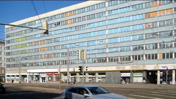 Alter Neubaublock. Fenster sind mit Meerestieren verziert, die Fassade besteht aus bläulichen Kacheln. Ebenerdig geschlossene Geschäfte.