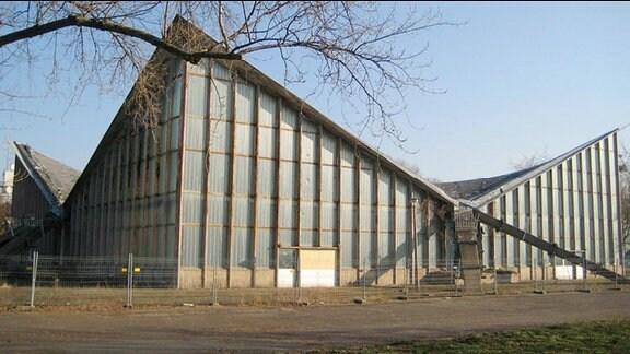 Hyparschale. Mehrzweckhalle aus dem Jahre 1969 im Magdeburger Kulturpark Rotehorn. Fassade besteht aus Glas, die vier Ecken des Gebäudes streben nach oben.