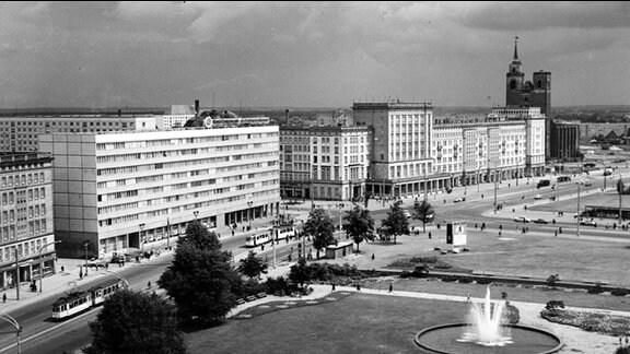 Die Wilhelm-Pieck-Allee in Magdeburg im jahr 1968, Aufnahme in Schwarz-weiß. Auf der linken Seite steht der sogenannte Blaue Bock, ein Arbeiterwohnheim mit blaugekachelter Fassade. Hinten rechts ist die Johanniskirche zu sehen. Deren rechter Turm hat keine Spitze. Die rechte Seite der Allee ist unbebaut, vorne befindet sich ein Springbrunnen in Betrieb.