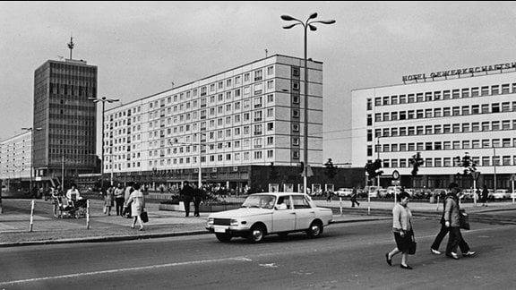 """Plattenbauten im Zentrum von Magdeburg in der damaligen Karl-Marx-Straße, von links nach rechts: das Hochhaus Haus des Lehrers, Restaurant Ratswaage, Hotel Gewerkschaftshaus. Passanten, parkende DDR-Fahrzeuge. Ein weißer Pkw """"Wartburg"""" fährt die Julius-Bremer-Straße entlang."""