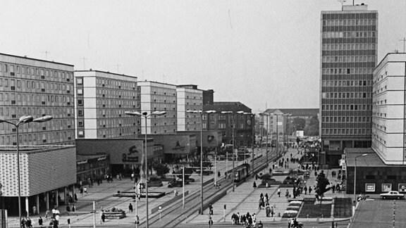 """Die Karl-Marx-Straße in Magdeburg in der DDR-Zeit. Aufnahme in Schwarz-weiß. Plattenbauten säumen die Fußgängerzone mit Straßenbahnverkehr. Hinten rechts steht das Hochhaus """"Haus des Lehrers"""". Davor ist das Gebäude mit dem Restaurant """"Ratswaage"""" zu sehen, im Vordergrund die Marietta-Milchbar mit Freisitz. Dei Straße ist großflächig mit Gehwegplatten belegt. Heute heißt die Straße Breiter Weg."""
