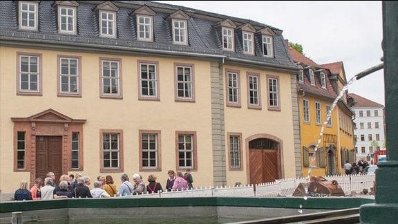 Goethehaus in Weimar. Gelb gestrichenes zweistöckiges Gebäude mit Sprossenfenstern, davor eine Touristengruppe.