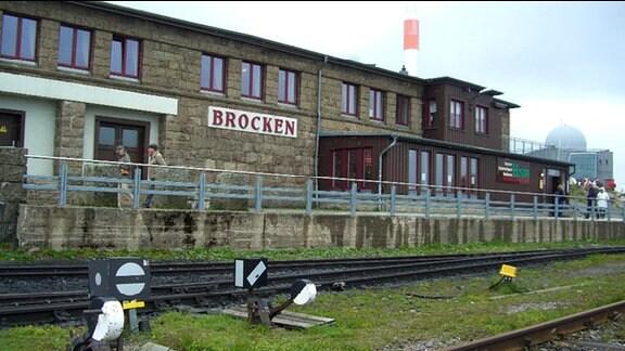 """Bahnhofsstation auf dem Brocken mit dem Schild """"Brocken"""", rote Schrift auf weißem Grund."""