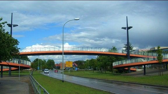 """Brücke in Wernigerode. Orangefarbene Fußgängerbrücke mit großen Bögen als Zugang verbindet die beiden Plattenbauwohngebiete Burgbreite und Stadtfeld in Wernigerode, im Volksmund nach einem früheren Bürgermeister """"Kilians Kreisel"""" genannt."""