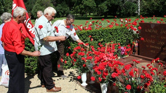 Menschen legen am Grab von Janos Kadar Blumen nieder