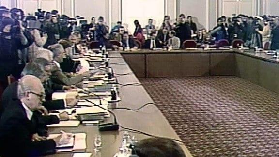 """Der sogenannte """"Runde Tisch"""" ist eigentlich eckig. Auf den Tischen vor Vertretern stehen Mikrofone."""