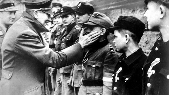 Eine der letzten Aufnahmen von Adolf Hitler vom 20. April 1945, seinem Geburtstag, zeigt ihn bei der Auszeichnung von Mitgliedern der Berliner Hitler-Jugend, die zum Ende des Zweiten Weltkrieges in Volkssturmeinheiten zusammengefaߟt wurden.