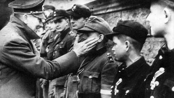 Adolf Hitler berührt das Gesicht von Wilhelm Willi Hubner