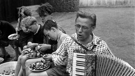 DDR 1950 - Akkordeonspieler unterhält Jungs beim Kartoffelschälen