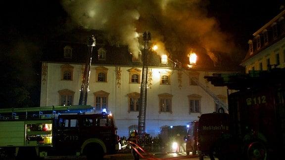 Löschfahrzeuge der Feuerwehr im Nachteinsatz - Flammen schlagen durchs Fenster während des Brandes der Anna Amalia Bibliothek in Weimar.