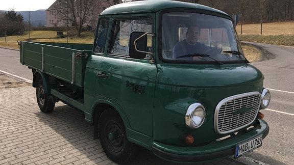 Grünes Auto mit einem lächelnden Mann hinter dem Steuer