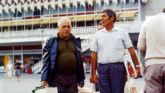 Maenner stehen am 20.05.1985 auf dem Alexanderplatz vor dem Centrum-Warenhaus.