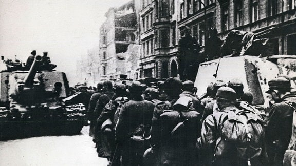 Deutsche Soldaten passieren auf dem Weg in die Gefangenschaft einen russischen Panzer.