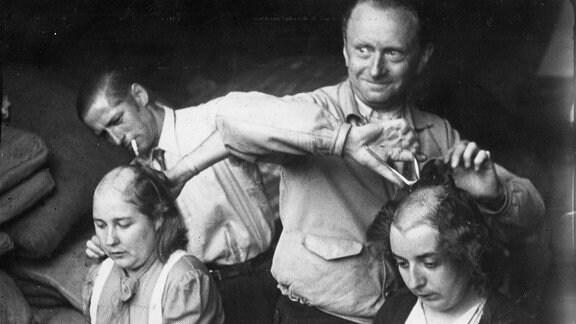Zwei Männer schneiden 2 Frauen die Haare ab.