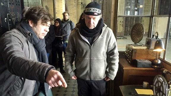 Zwei Männer stehen in einer Art Fabrikhalle vor einem Tisch mit einem Morse-Apparat. Beide Männer sind warm angezogen, einer mit Schal. Im Hintergrund steht eine Frau mit einer aufgeklappten Schreibmappe, neben ihr wartet ein anderer Mann.