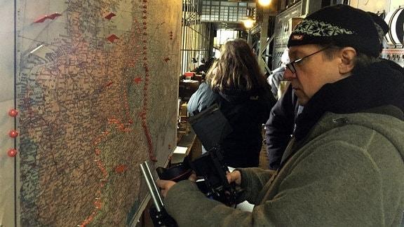 Ein Mann steht seitlich vor einer Landkarte, auf der rote Pins Linien markieren