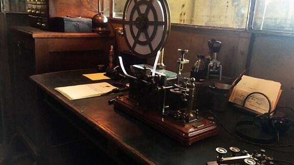 Großer Holztisch, auf dem eine Apparatur steht. Sie ist voller verschiedener Knöpfe. Obenauf ist ein Rad befestigt, in das eine Papierrolle eingespannt ist.