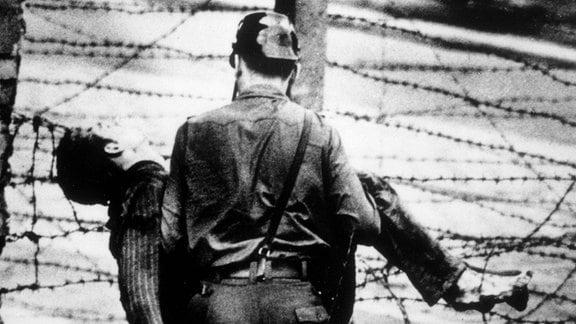 Ein Grenzsoldat trägt einen Mann (Peter Fechter)