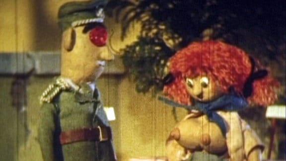 Zwei geknetete Figuren - vor einem Polizistenpuppe statt eine barbusige Frau mit roten Haaren.