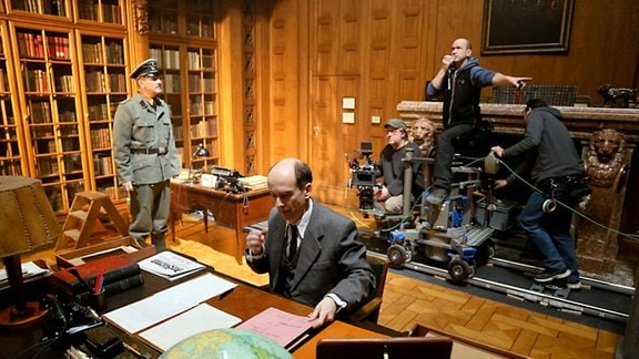 Ein Mann im Anzug sitzt an einem Schreibtisch, hinter ihm steht ein Kamerateam.