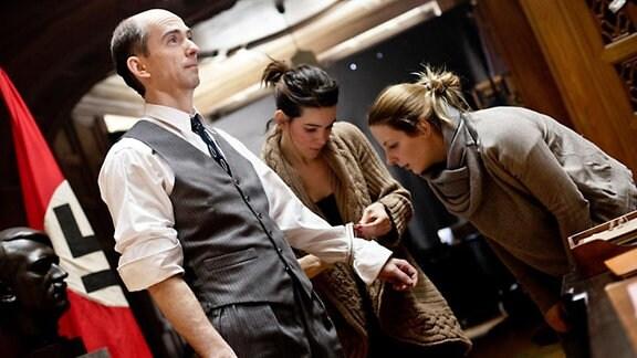Ein Mann im Anzug, neben ihm stehen zwei Frauen.