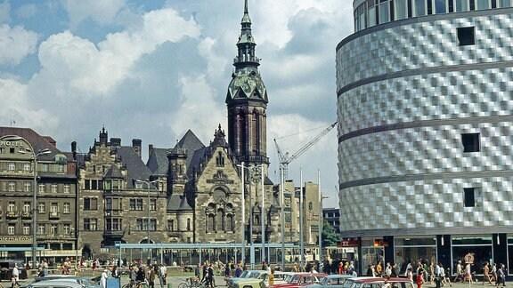 Parkplatz am Richard-Wagner-Platz, rechts Konsument Warenhaus am Brühl, dahinter Hotel International und Evangelisch-Reformierte Kirche am Tröndlinring 1969