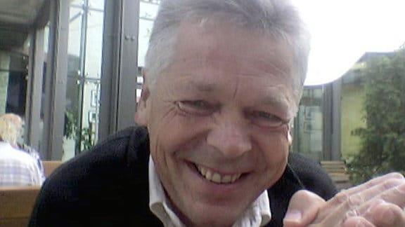 Ein Mann sitzt an einem Tisch und schaut lachend in die Kamera.