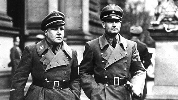 Zwei Männer im Gleichschritt in langen Uniformmänteln