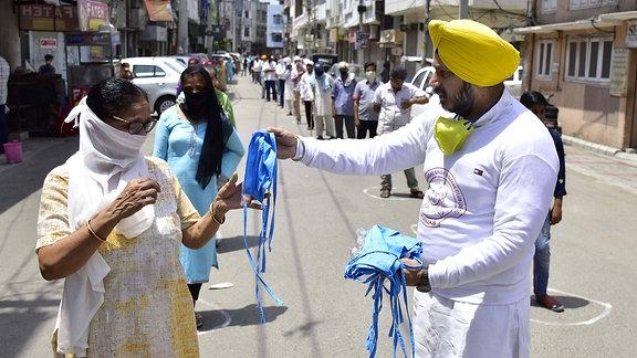 Ein Mann verteilt in Katra Sher Singh Gesichtsmasken an die Menschen
