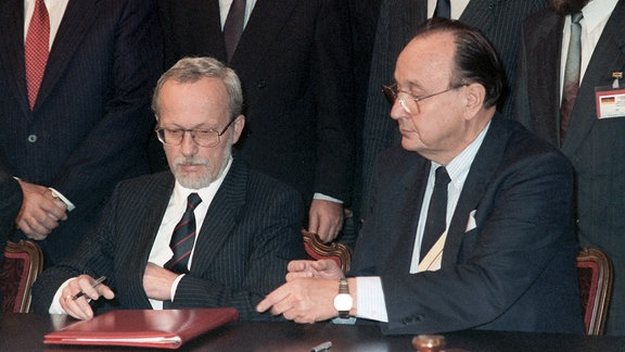 """Der deutsche Außenminister Hans-Dietrich Genscher (r) und sein DDR Premierminister Lothar de Maiziere (l) während der Unterzeichnung des 2 plus 4 -Vertrages. Im Moskauer Hotel """"Oktober"""" unterzeichneten am 12. September 1990 die Außenminister der beiden deutschen Staaten und der vier Siegermächte den Vertrag über die äußeren Aspekte der deutschen Einheit."""