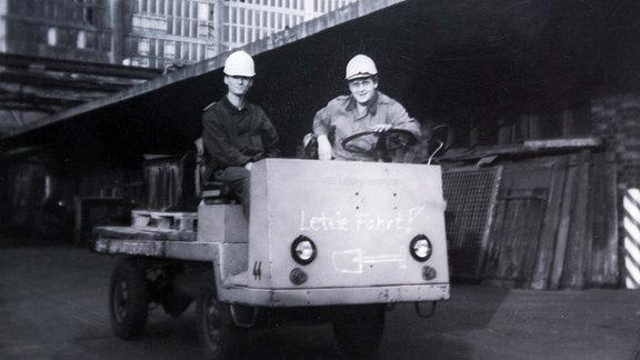 Zwei Bausoldaten sitzen auf einem kleinen offenen Transporter.