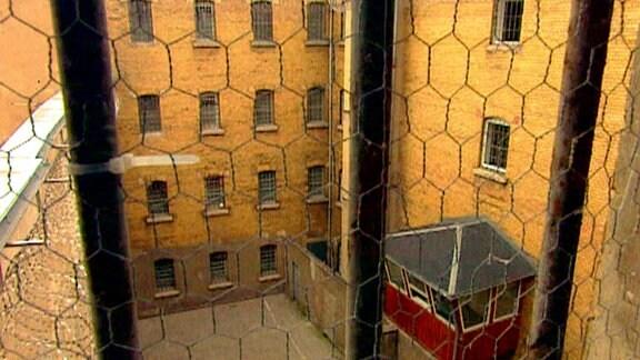 Blick durch vergittertes Fenster in Gefängnishof
