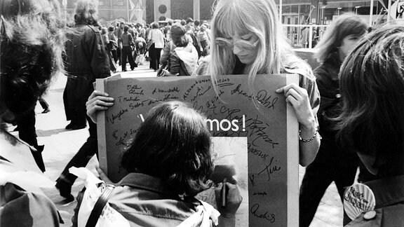 Eine Frau setzt ihre Unterschrift ein Plakat, welches Solidarität für Salvador Allende fordert.