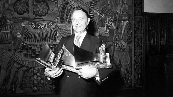 """Produzent Wolf Hartwig mit den Auszeichnungen """"Goldene Leinwand"""" in der Hand"""