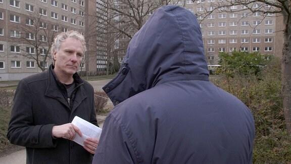 Zwei Männer stehen im Gespräch vertieft vor einem Hochhaus. Um nicht erkannt zu werden, wurde ein Mann mit Kaputze von hinten gefilmt.