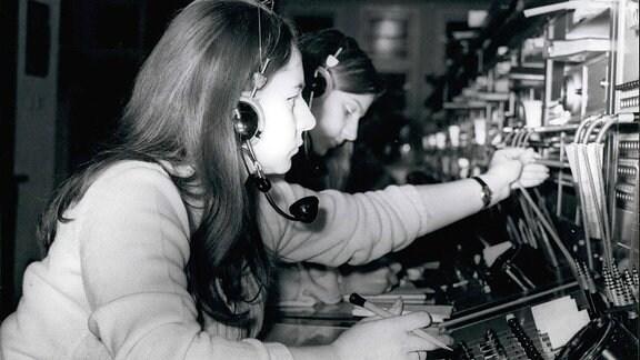 Eine Frau bedient eine Anschlussbuchse. Sie trägt Kopfsprechhörer und hält einen Stift in der Hand.