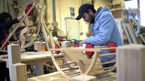 Ein Mann arbeitet an einer Werkbank an einer Rollschaukel.