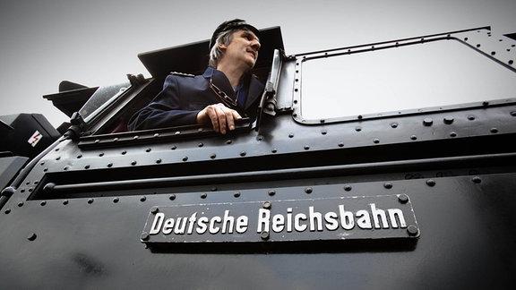 Ein Lokführer schaut aus dem Führerstand einer Dampflok.