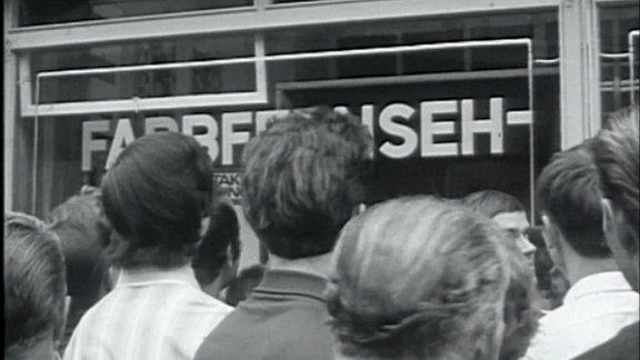 Menschen drängeln sich vor einem Fernsehgeschäft welches Farbfernsehgeräte anbietet