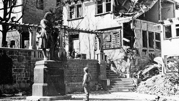 Ein US-Soldat steht im April 1945 in Eisenach vor der Statue des deutschen Komponisten Johann Sebastian Bach.