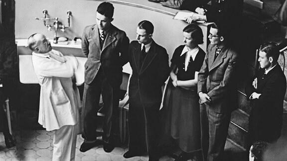 Professor Ferdinand Sauerbruch unterhält sich mit Medizinstudenten im Hörsaal der Charite in Berlin, ca. 1935