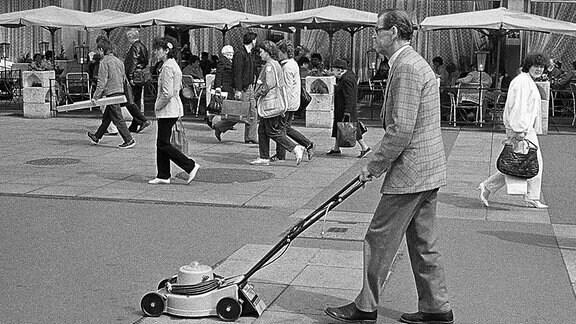 Ein Mann geht mit einem Rasenmäher auf der Straße.
