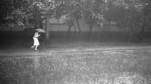 Eine Frau rennt mit Regenschirm durch den Regen.