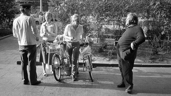 Ein Polizist und drei Personen unterhalten sich auf der Straße.