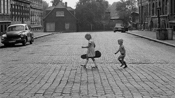 Zwei Kinder laufen über einer gepflasterte Straße.