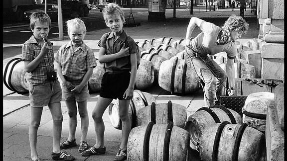 Drei Jungen stehen neben Fässern und schauen in die Kamera.